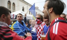 Kosovo and Croatia's fans draped in national flags sing together ahead of the World Cup Group I qualifying match between Kosovo and Croatia in main square in Shkoder, Albania on Thursday Oct. 6, 2016. (AP Photo/Visar Kryeziu)